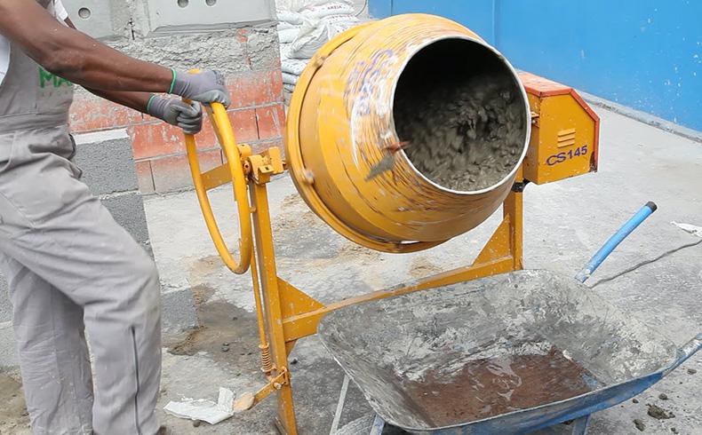 Operário manuseando uma máquina de preparar concreto