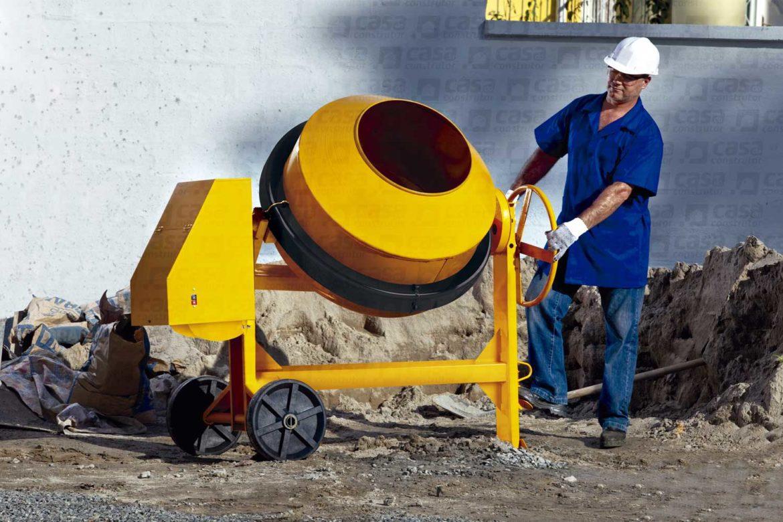 operário de obra manuseando uma máquina de preparar concreto