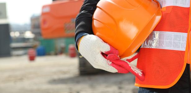 Operário segurando um capacete de construção