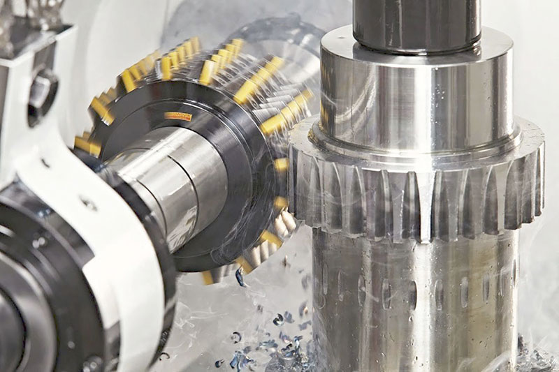 Uma máquina fresadora fazendo a modificação de uma peça de metal, transformando-a em uma engrenagem