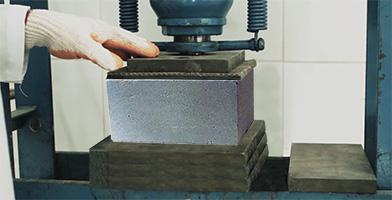 Um bloco de concreto sendo testando no quesito resistência à compressão
