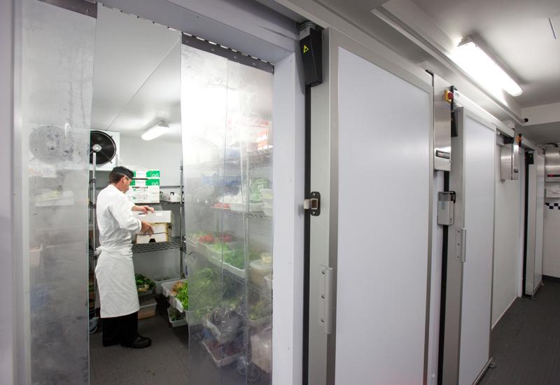 Funcionário dentro de uma câmara frigorífica mantendo alimentos
