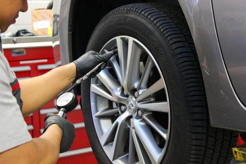 mecânico revisando pneus de um automóvel