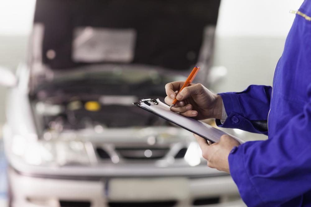 mecânico realizando a revisão de um modelo de carro