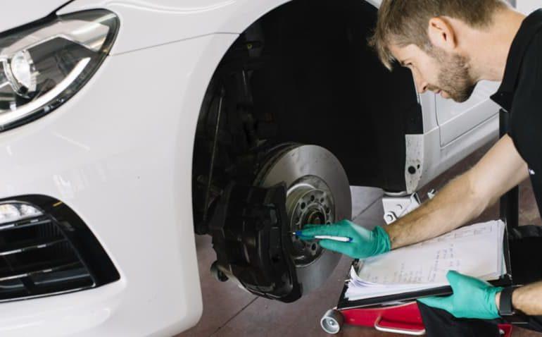 Mecânico fazendo revisão nos pneus de um carro