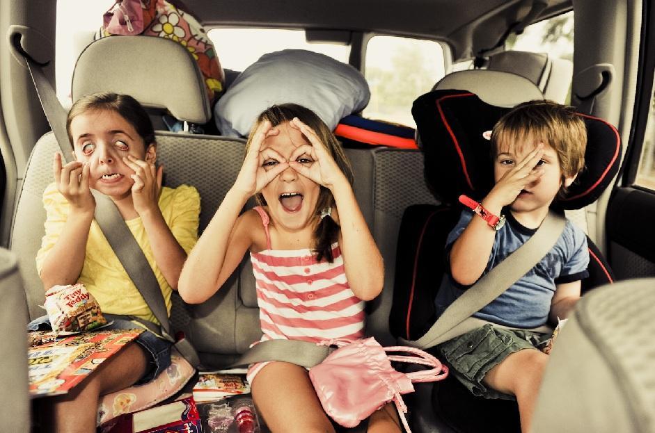 parte de trás de um veículo com três crianças no banco de trás brincando