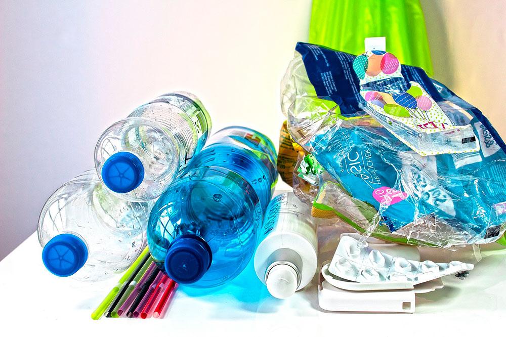 resíduos sólidos plásticos como garrafas, canudos, embalagens, caixas de remédios, lacres, caixas de shampoo em cima de uma mesa