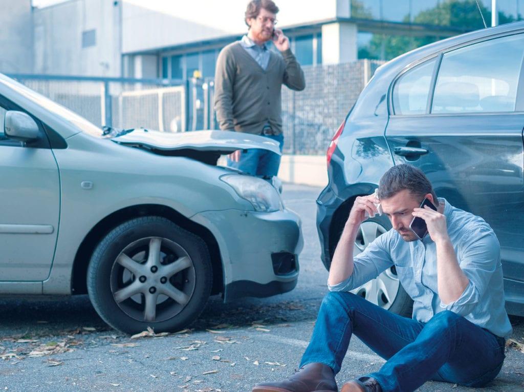 motorista sentado no chão falando ao telefone, e o seu carro acidentado no fundo
