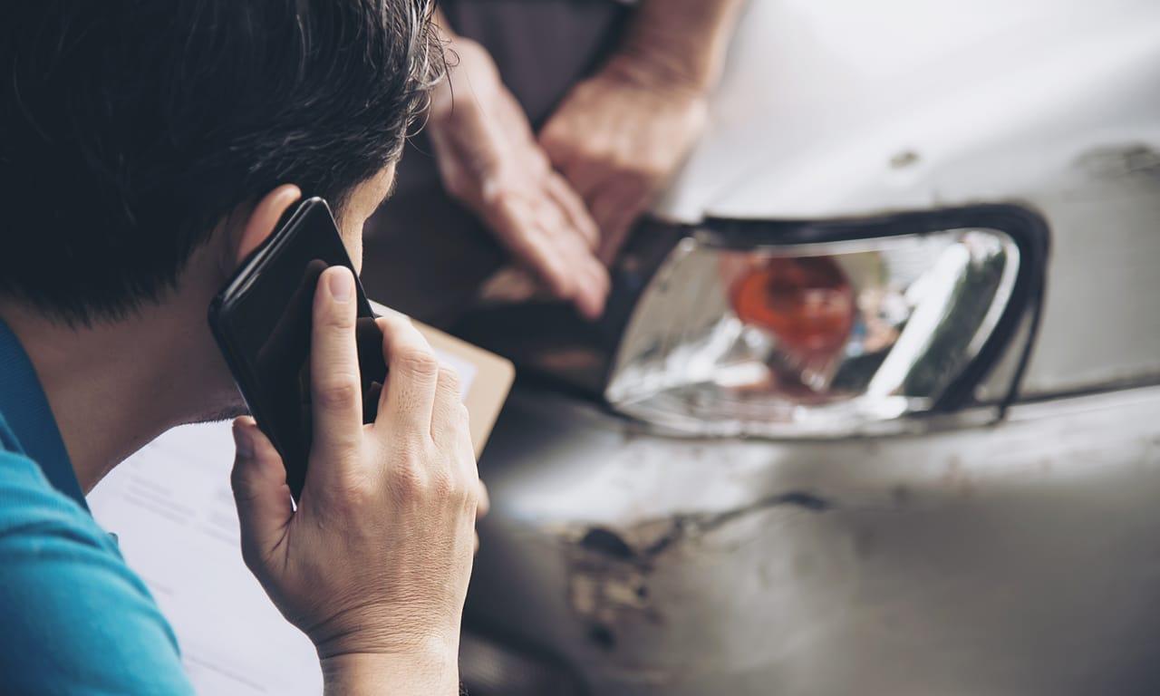 motorista falando ao celular com o carro sinistrado a sua frente