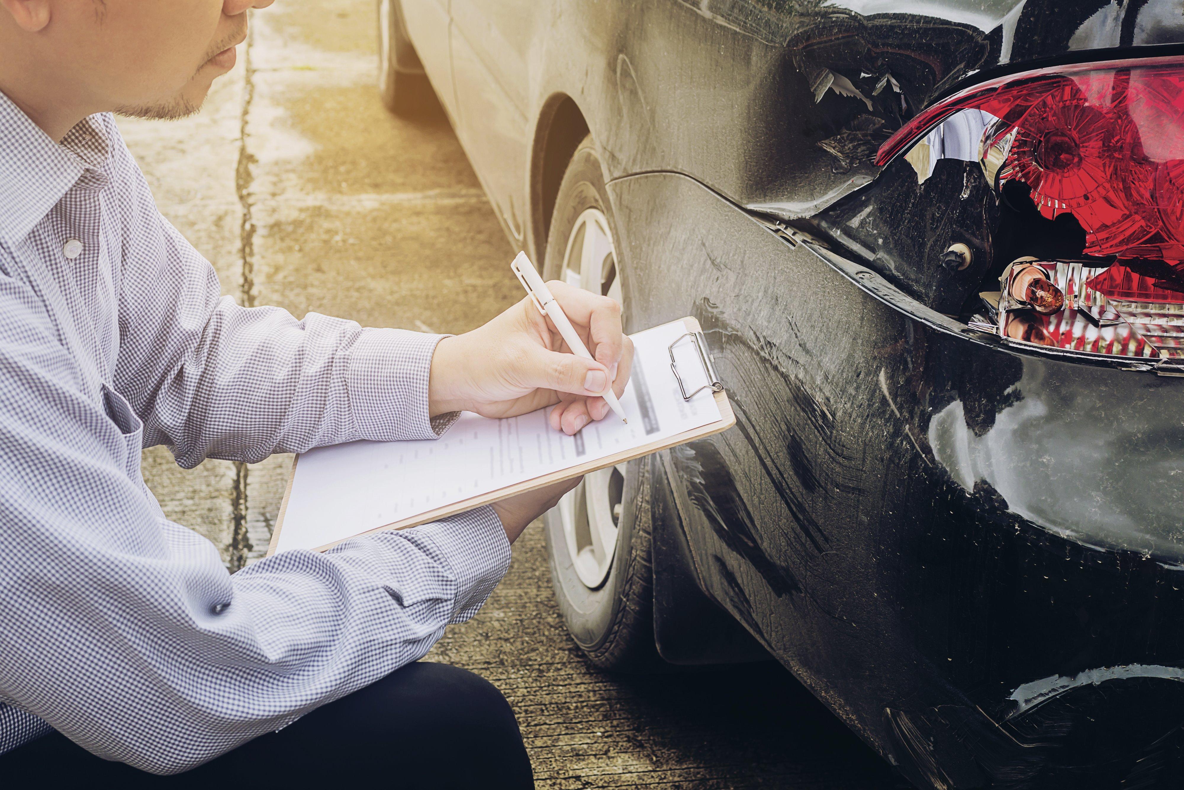 homem fazendo a avaliação de sinistro de carro