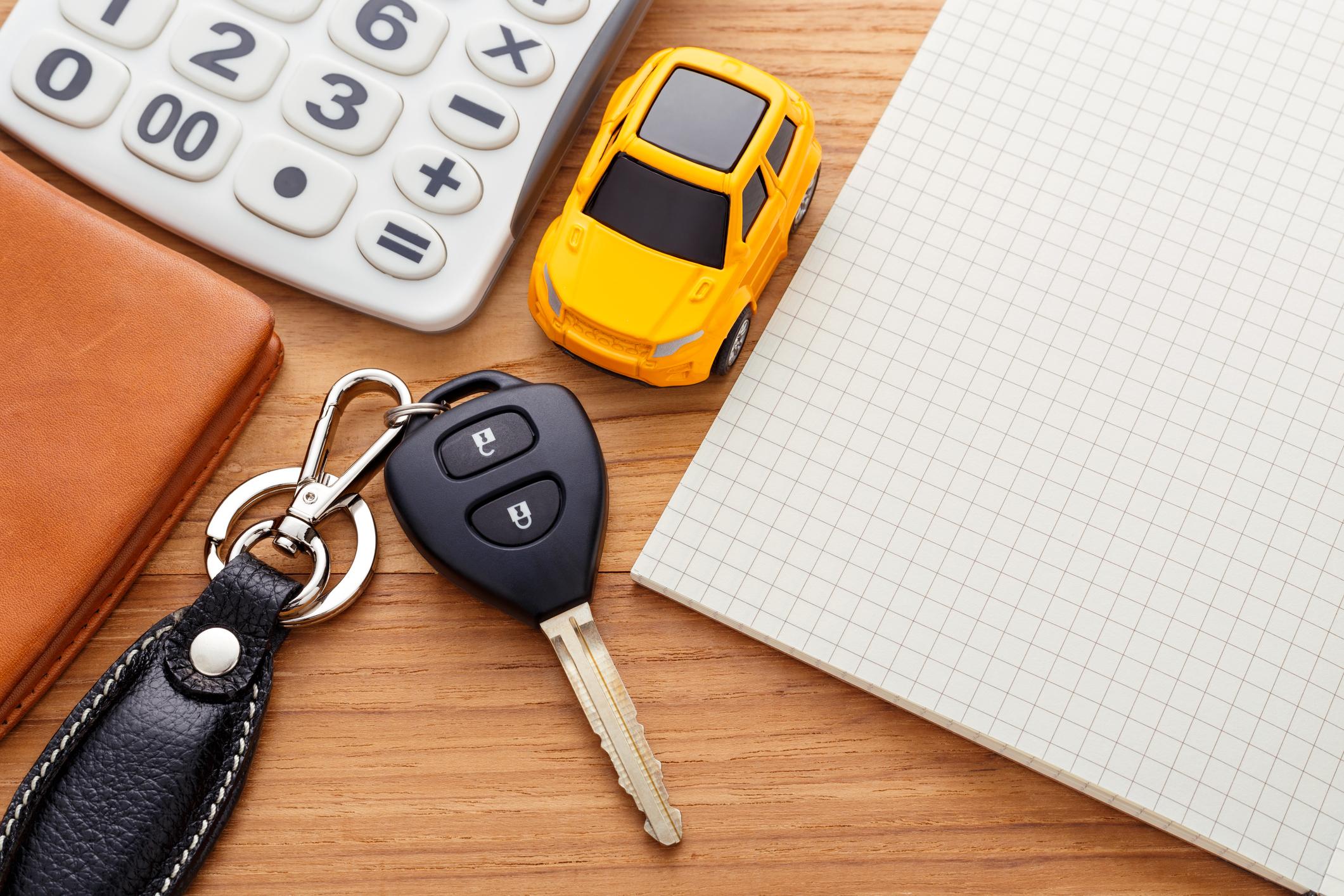 uma mesa com uma chave de carro, um carro em miniatura, uma calculadora, uma carteira e um caderno