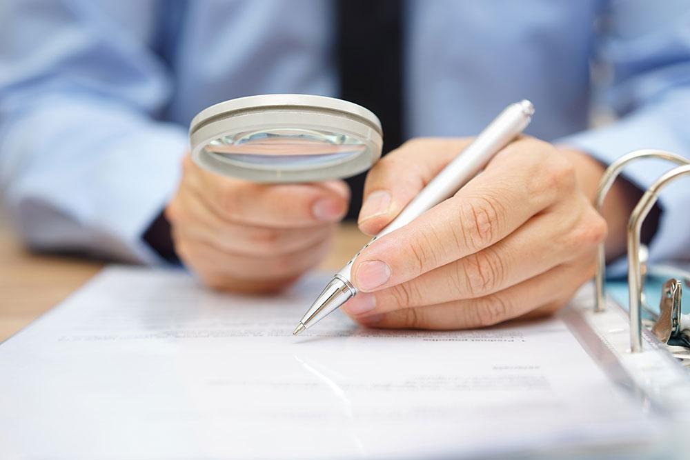 moço assinando um contrato com a ajuda de uma lupa