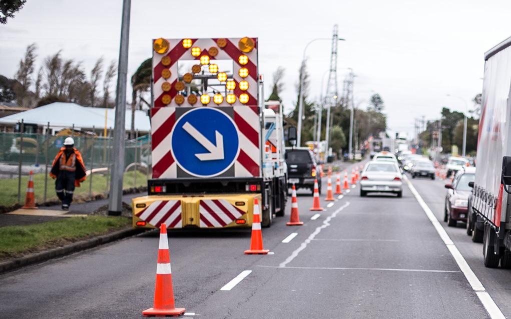 Placa de sinalização na estrada informando aos motoristas para mudarem de faixa.