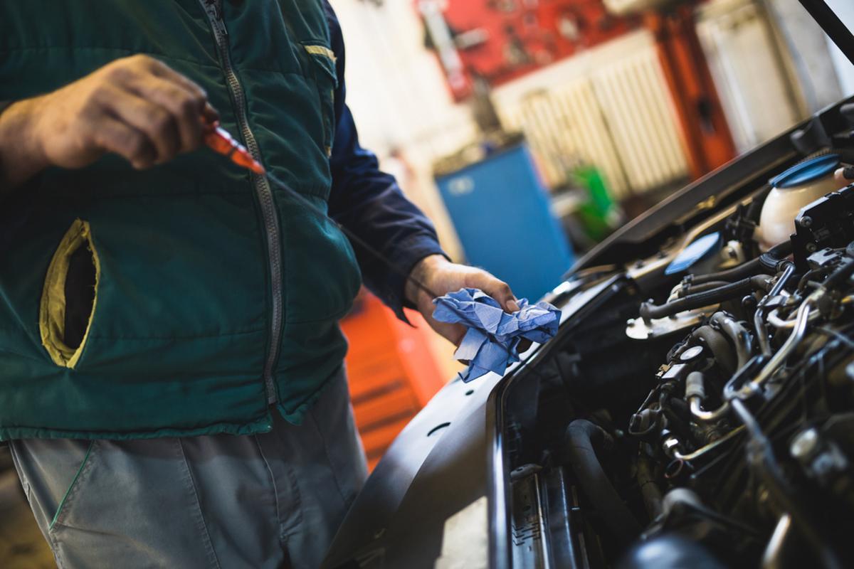 Mecânico analisando o nível de óleo do veículo. Dessa maneira, é possível saber se o óleo está abaixo ou se está a ponto de troca.